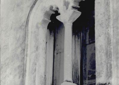 FINESTRA VICO PONTONE. Al secondo piano di un vano di abitazione si può osservare una bifora a doppio arco a tutto sesto, poggiante su una colonnina cilindrica con capitello modanato; all'interno degli archi sono presenti quattro dentelli ed inoltre l'apertura è arricchita da una cornice che ne segue il profilo.