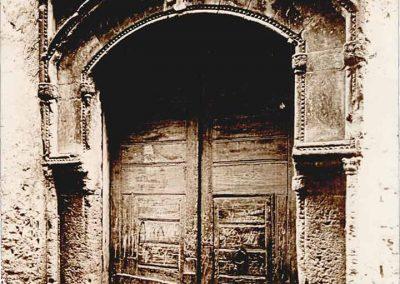 ANTICO PORTALE SCOMPARSO. Questa fotografia riproduce l'antico portale di casa Marzano così come si presentava prima della sua totale distruzione, avvenuta nel 1943.  Informato ad uno stile diverso rispetto al gusto che pervade l'intera fabbrica, presenta un arco ribassato inscritto in una cornice rettangolare con foglie d'acanto nei pennacchi, arricchito di colonnine con capitelli a cespuglio negli stipiti e serti di diamanti nelle cornici. Al centro presenta una croce gerosolimitana ed è sormontato dallo stemma dei Marzano.