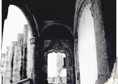 VEDUTA INTERNA DEL LOGGIATO -PORTALE BICUSPIDATO CON ARCO DUE VOLTE INFLESSO - Da questa immagine del loggiato si può notare uno degli elementi architettonici e sculturali più importanti ancora esistenti in casa Marzano: il portale bicuspidato, attraverso il quale si accedeva alla sala delle udienze, ambiente andato completamente distrutto. Tale portale, arricchito da numerose cornici, è costituito da un caratteristico arco due volte inflesso, sormontato da tre stemmi araldici. Questo importante elemento di casa Marzano, presenta notevoli somiglianze con il portale tre volte inflesso presente a Capua, nel palazzo Antignano, probabile opera, anch'esso, come questo ancora esistente in Carinola, di Guillem Sagrera.