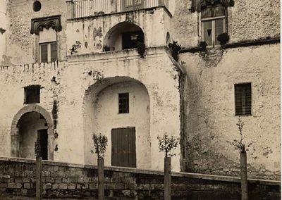 FACCIATA SU PIAZZA VESCOVADO - COPPIA DI FINESTRE. Poste sulla facciata sud del fabbricato, sono costituite entrambe da una cornice a a cui sono sospesi pendagli lapidei. Una differenza sostanziale è attualmente riscontrabile tra le due aperture: essendo stata, la prima, trasformata in un balcone ed avendo recuperato, la seconda, l'originaria destinazione di finestra.