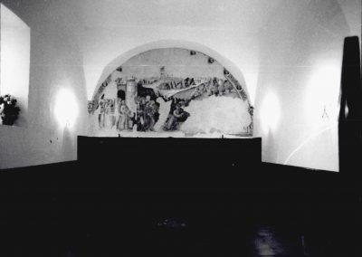 """CONVENTO SAN FRANCESCO -     AFFRESCO REFETTORIO.  Nell'antico refettorio del convento, un tempo voltato a crociera, posto in un'ampia luna di fronte all'entrata, si può osservare il prezioso affresco post-giottesco nel quale è raffigurato il tema della """"salita al Calvario"""". Fanno da cornice al tema centrale un corteo di santi francescani guidati da S. Francesco ed un altro, appena riconoscibile a causa delle non poche abrasioni, di clarisse guidate da S. Chiara, posto simmetricamente al primo. Inoltre, in alto a destra, è visibile il complesso conventuale; mentre a sinistra emergono, alle spalle del corteo di santi francescani, bastioni angioini e l'arco della porta urbana riecheggiante quello di Alfonso d'Aragona. Una cornice di putti alati e festoni, che scandiscono gli intervalli tra i medaglioni con effigi di santi apostoli, completa l'opera di autore ignoto."""