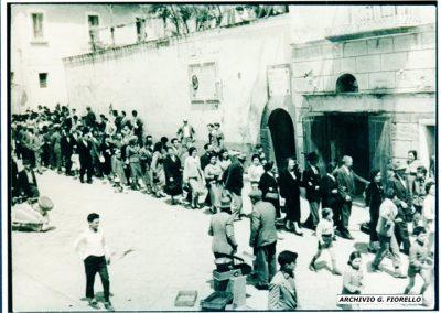 Casale- la processione, sullo sfondo la storica targa dedicata a N. Trabucco